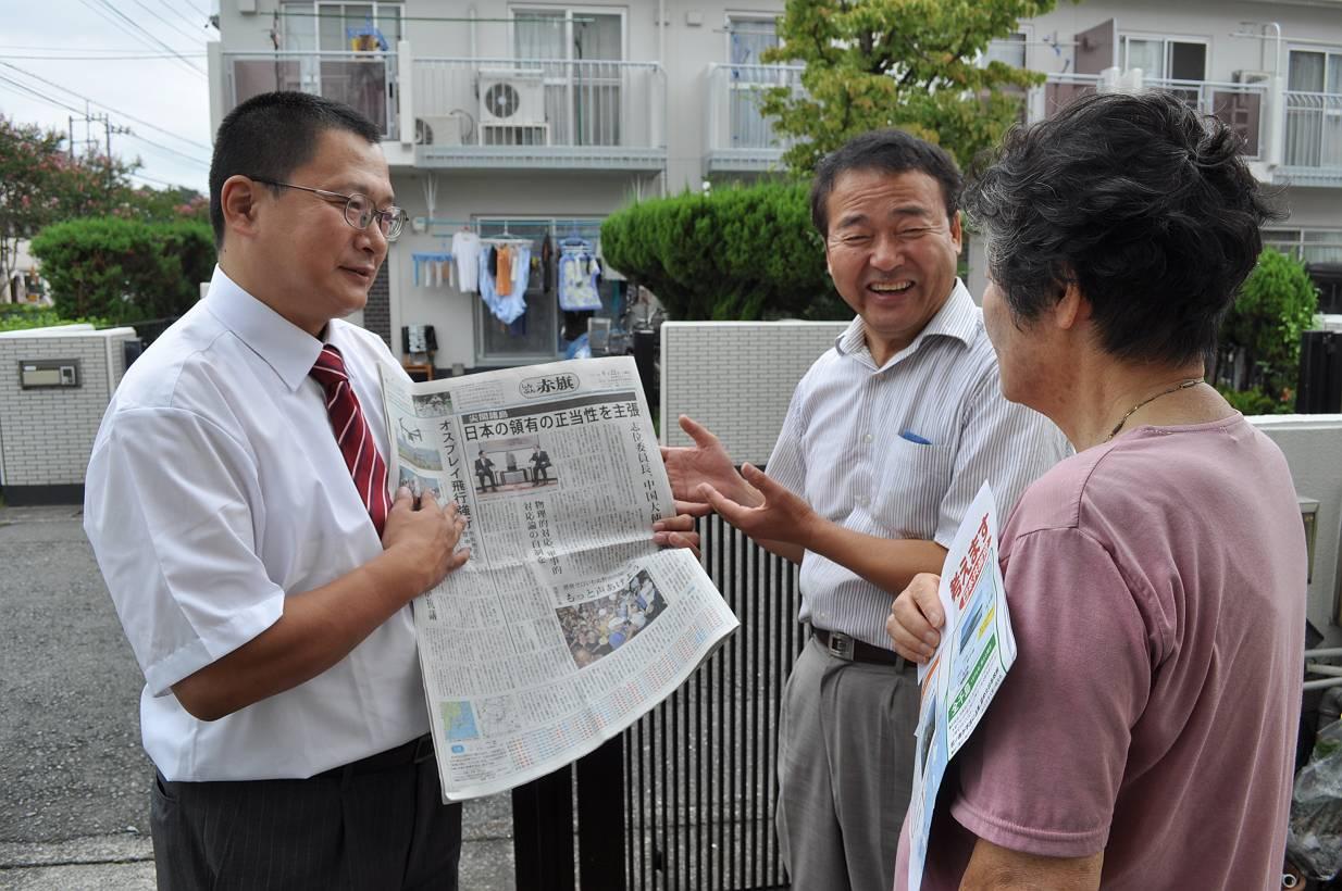 市民に赤旗新聞の記事を紹介する工藤武予定候補(左)と猪股市議(中央)