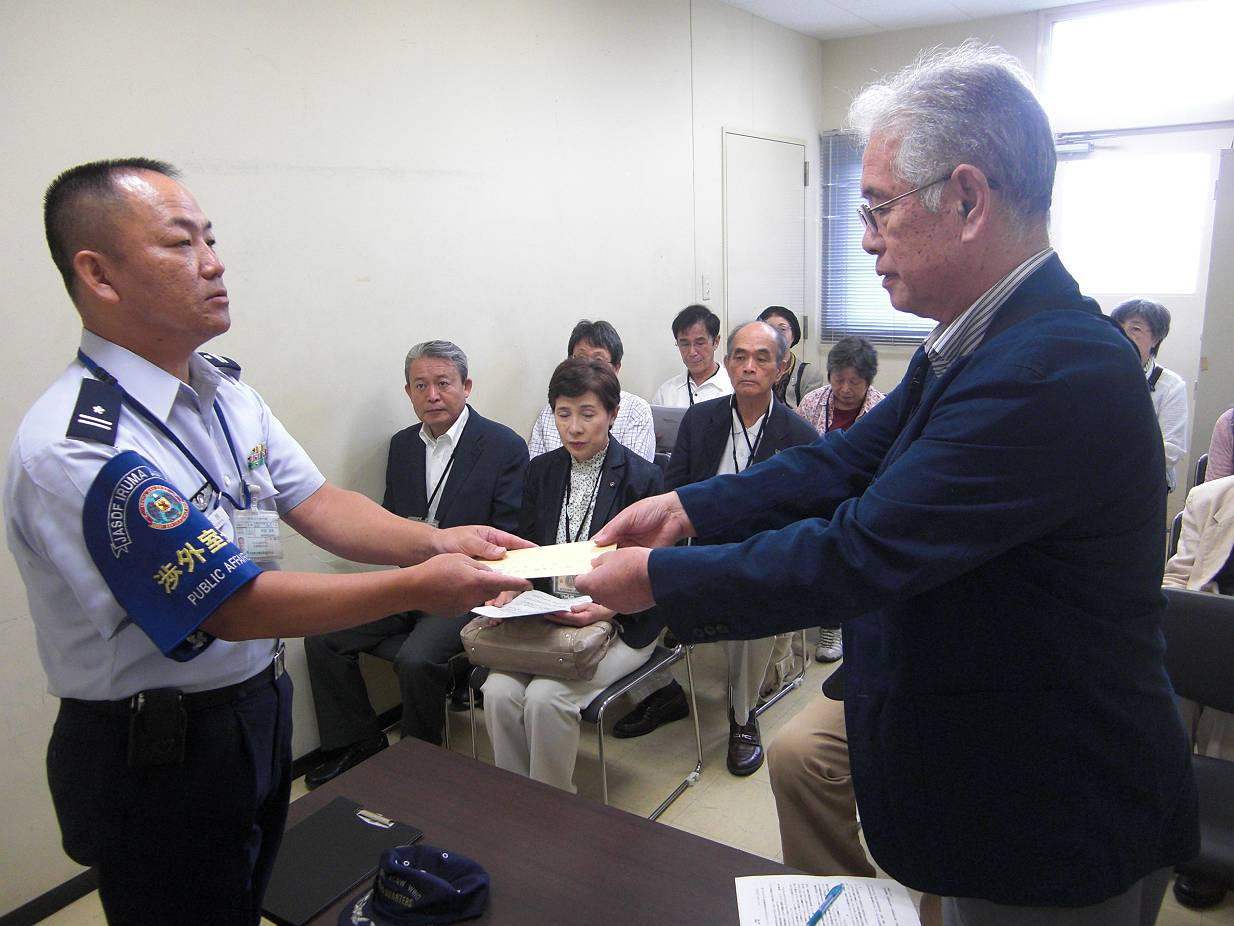 要望書を手渡す飯島代表(右)と後方は要請団。入間基地にて10月2日。