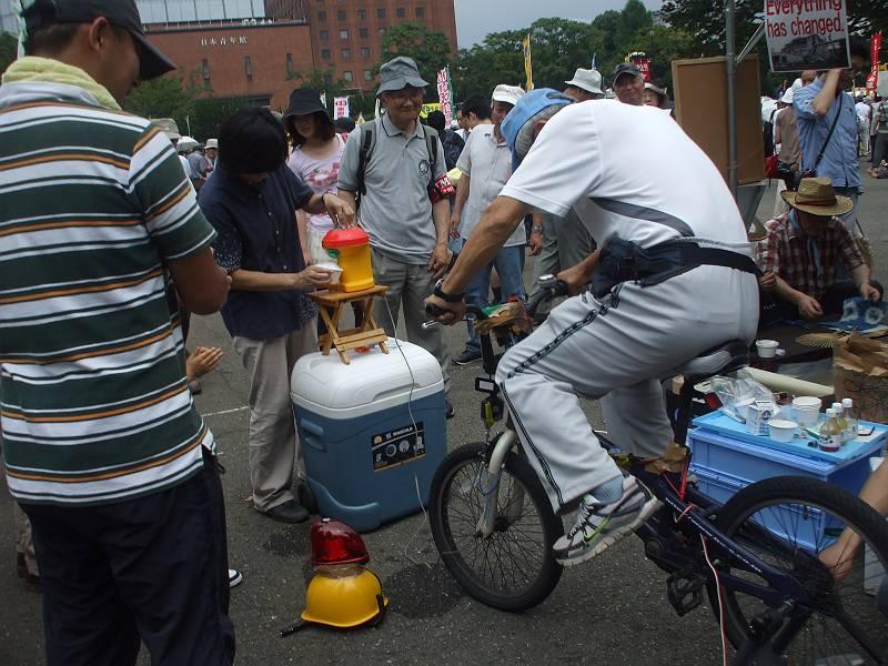 各ブースでは原発問題の学習会や、福島の子供たちの様子を展示したパネル、原発の安全性をうたっている学校教材の展示など、様ざまな企画が行われていました。<br> <br> 写真は自転車発電(!)の実演(^^)<br> 自転車をこいで発電し、機会を動かしてかき氷を作っていました。興味深そうに子供たちが見守っていました〜
